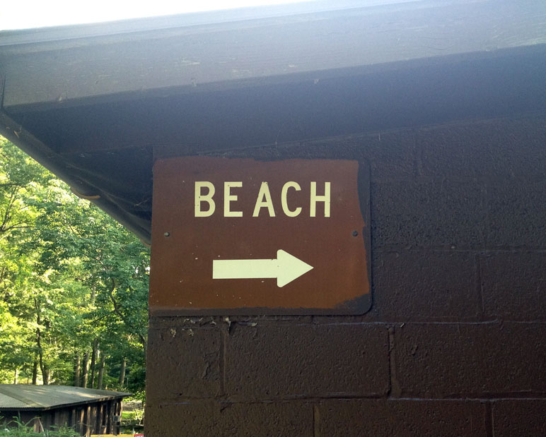 Sign directing guests to the beach area at Sebago Cabin Camps, in Harriman State Park, New York.