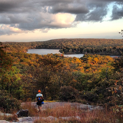 Hiker overlooking fall foliage viewpoint in Harriman State Park, New York. Photo courtesy of Instagram user #woomas.