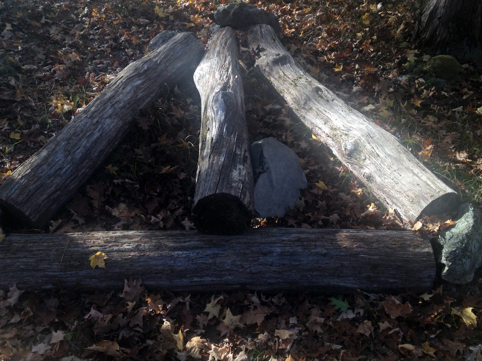 Four logs form an arrow at the intersection of an unmarked trail to Stahahe High Peak, and Island Pond Road, a woods road in western Harriman State Park.