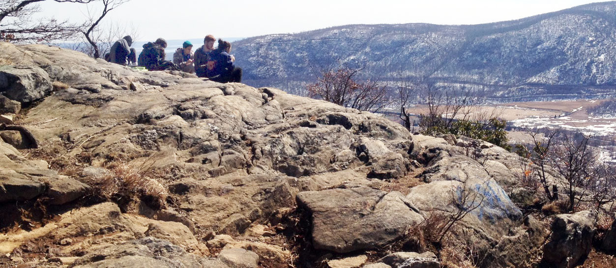 In springlike weather, a group of college students has a picnic high atop Anthony's Nose, in the Hudson Highlands.