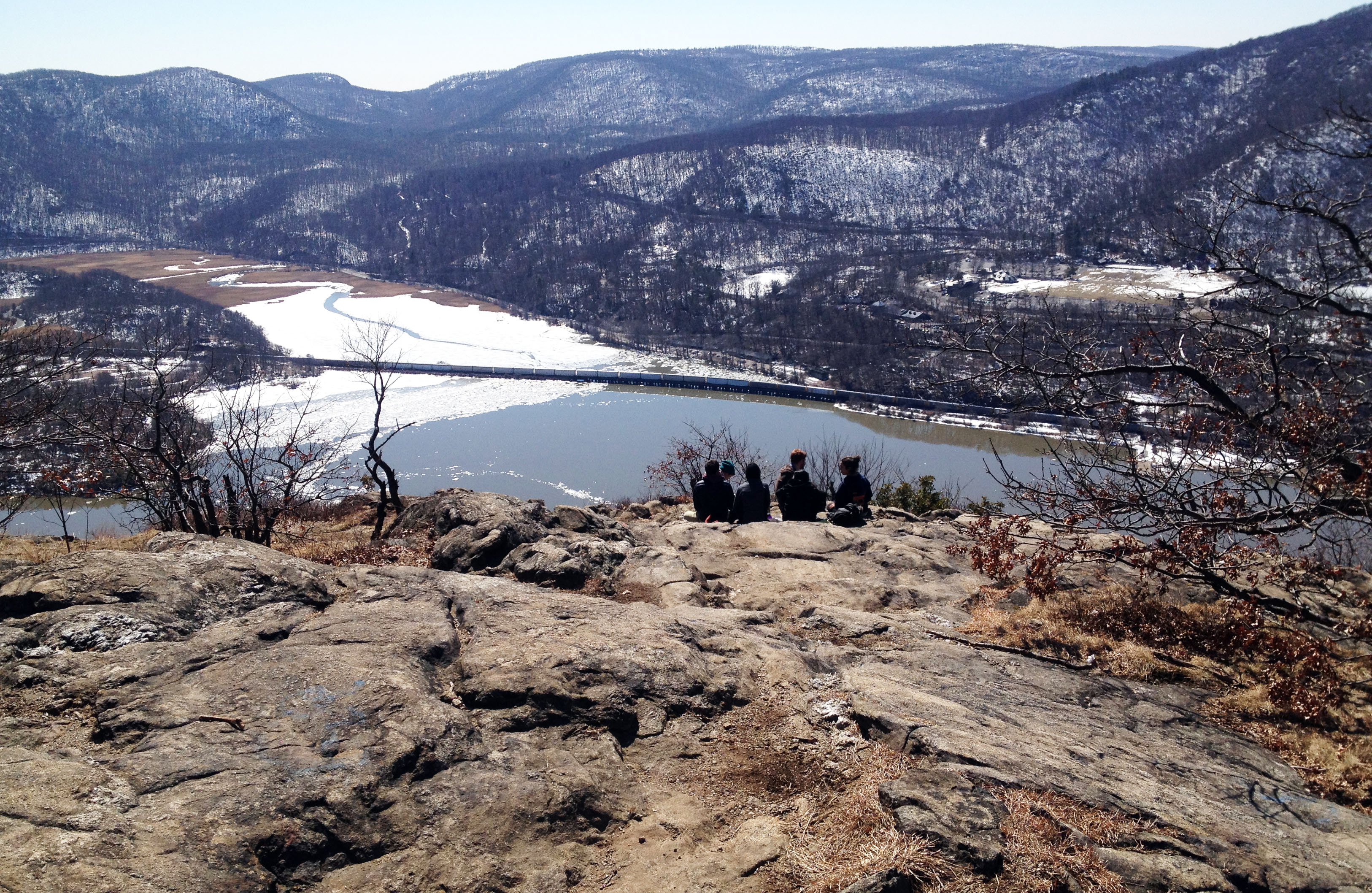 Students sit on the cold rocks of Anthony's Nose, overlooking the Hudson River in spring.