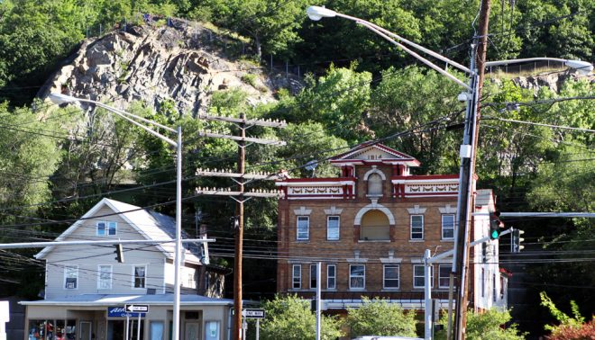The looming, exposed rock of Nordkopf Mountain in Suffern, New York. Old telegraph poles still display their porcelain insulators.
